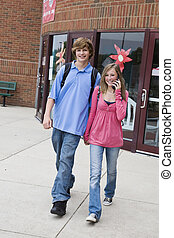 Teens - Young teenage boy and girl holding hands while...