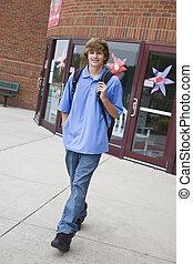 Teens - Teenage boy leaving school building