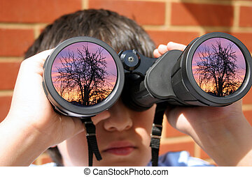 Boy with binoculars - Boy using his binoculars, focus on...