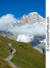 Trekker walking along a mountain path, in background the...