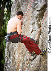 Male Climber Repelling - A male climber repells down a rock...