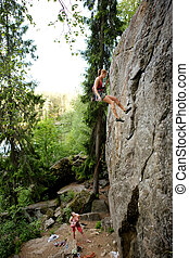 Two climbers - A female climber, repelling down a steep rock...