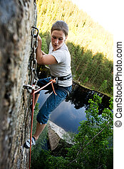 Fear - A climber at the top of a ledge looking down with...