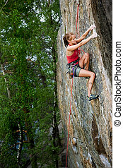 Female Climber - An eager female climber on a steep rock...