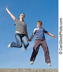 jumping family. Mum and the son with blue sky at background