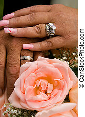Newly Weds Holding Hands with Rings and Flowers
