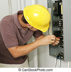 Electrician and Breaker Panel - An electrician working on an...