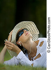 Summer Music - A beautiful dark haired woman laying in a...