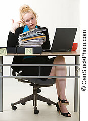Overworked - Blond business woman sitting at desk pointing...
