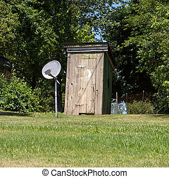 modern outhouse - an out house with a dish tv reciever in...