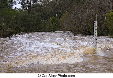 Flash Flooded Road - Road covered by fast flowing flood...