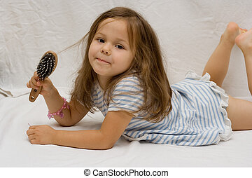 Hair care - the little cute girl brushing her hair