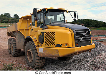 Dumper Truck - Large yellow dumper truck standing idle on a...