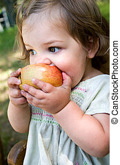 Healthy Snack - a dirty little girl eating a nice crispy...