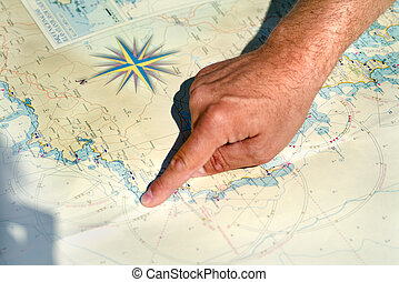 hand and map - hand pointing to a place on a marine map