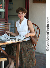 Woman with newspaper - Mature woman reading newspaper in a...