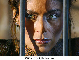 Confinement. - A woman with striking eyes stares out between...