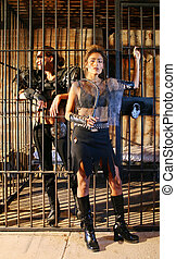 Jailer and Captive. - Futuristic woman jailer guards a woman...