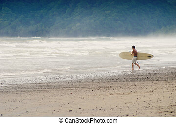 Heading Out - Surfer with his board heads for the water