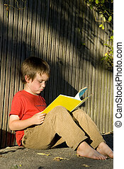 boy reading book - boy in red shirt reading book outside