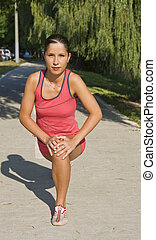 Warming up - Young woman doing warming up movements before a...