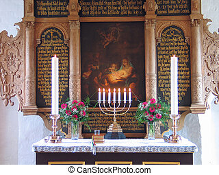 Alter in a church with candles and flowers during Baptismal...