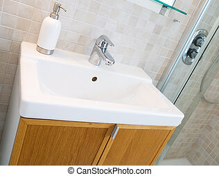 Bathroom Sink - A standard new bathroom sink with tiles on...