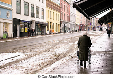 Old Woman with Walker - An old woman walking outdoors in the...