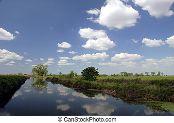 Irrigation Canal and Farmland under Puffy White Summer...