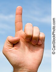 one. hand gesture with blue sky at background