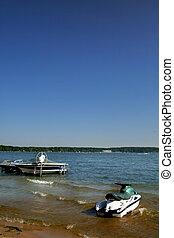 Boats At Lake Shore - One boat and water scooter at lake...
