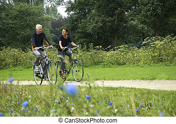Seniors Biking - Active senior couple biking in the park,...