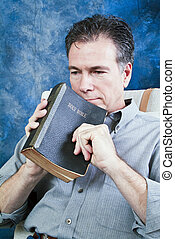 Time for Reflection - A man holding an old bible, with an...
