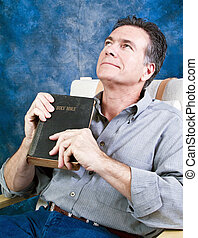 Welcome Guidance - A man holding an old bible with a look of...