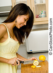 Slicing Lemons - A beautiful young Asian woman slicing...
