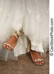 Wedding shoes on barefooted legs of the bride