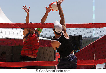 Beach Volleyball - Beach volleyball players blocking and...