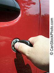 locking up - detail photo of a mans hand locking up a red...