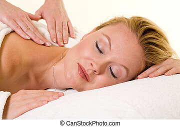 Having a massage - Attractive blond woman laying on stomach...