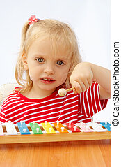 Rainbow xylophone - Little girl wearing striped red t-shirt...