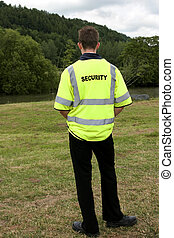 Security Man - Male security guard standing alone in rural...