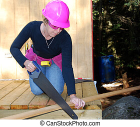 Sawing Wood - female construction worker saws wood with pink...