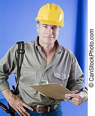 Construction worker with hard hat and clip board standing in...