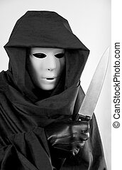 Creepy Halloween - A man in a mask and hooded cloak, holding...