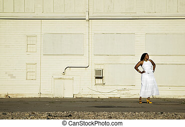 Waiting by a Warehouse - African American woman waiting...