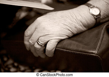 Old Hand - A detail of an old womans hand on her purse using...