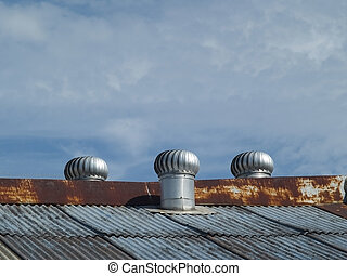 Three ventilators on a roof - Three wind-driven, rotating...
