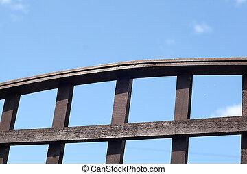 wooden trellis set against a blue sky