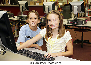 Kids in Computer Lab - A boy and girl doing research in the...