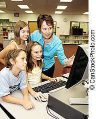 Kids Learn Computer - A teacher instructing kids on using...